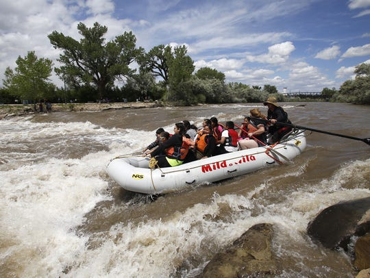 Festival goers ride a raft down the Animas River on
