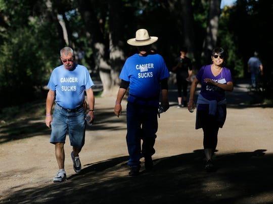 From left, Ron McNeal, Monica Sorrels and her husband Steve Sorrels walk, Saturday, Sept. 12, 2015, during the San Juan County Medical Foundation's annual Cancer Walkathon in Berg Park in Farmington.