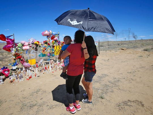 Clara Bates, holding her grandson Luciano Eriacho, and daughter Johanna Wilson, both from Ojo Amarillo, pay their respects at a memorial for Ashlynne Mike May 4, 2016, on Navajo Route 36 in Lower Fruitland.