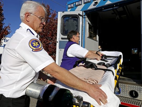 Paramedics John Reese, left, and Matt Moon display equipment used inside an ambulance in Farmington on Nov. 23, 2105.