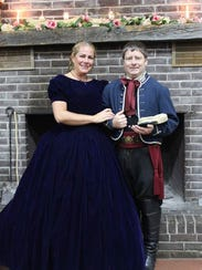 Nikki and John Walsh pose for a portrait by the fireplace.