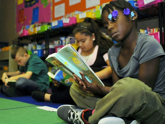Alaythia Solomon, 9, right, and her classmates Jack Wingert, 9, and Tatiyana Carrillo, 9, read books Thursday at Andrew Buchanan Elementary School. Chambersburg Area School District elementary school classes received 350,000 worth of donated books.
