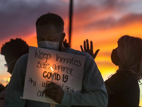 Family members of inmates incarcerated in the Utah Department of Corrections' prison system hold candles and say a prayer following a rally outside the Department of Corrections office in Draper on Tuesday.