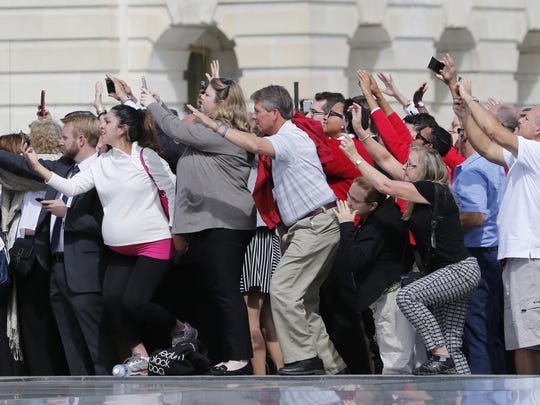 Congressional staffers and guests strain to view and photograph the departure of Pope Francis on Capitol Hill. The pope addressed Congress on Thursday, Sept. 24, 2015.