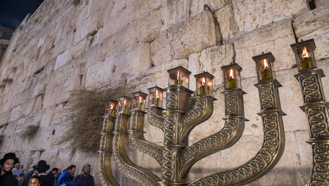 A large candelabra lit with the eight candles, or flames from oil lamps, at the Western Wall, Judaism's holiest site, in the Old City of Jerusalem, Dec. 19, 2017.