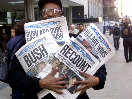 In this Nov. 8, 2000 file photo, Willie Smith holds four copies of the Chicago Sun-Times, each with a different headline, in Chicago, reflecting a night of suspense, drama and changes in following the presidential race between Vice President Al Gore and Texas Gov. George W. Bush. What happens if America wakes up on Nov. 9 to a disputed presidential election in which the outcome turns on the results of a razor-thin margin in one or two states, one candidate seeks a recount and the other goes to court?