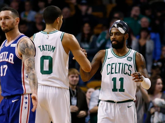 Boston Celtics' Kyrie Irving and Jayson Tatum (0) congratulate each other as Philadelphia 76ers' JJ Redick walks off the court after the Celtics' 108-97 win in an NBA basketball game in Boston on Thursday, Nov. 30, 2017. (AP Photo/Winslow Townson)