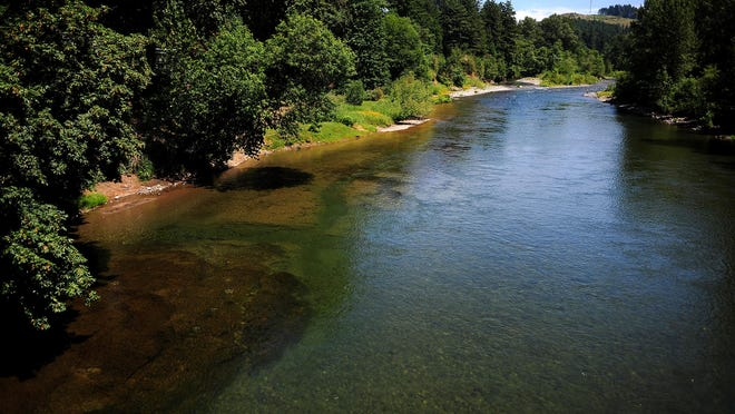 The Santiam River flows as seen from the Albany-Lyons Highway bridge on Monday, June 22, in Mehama, Ore.