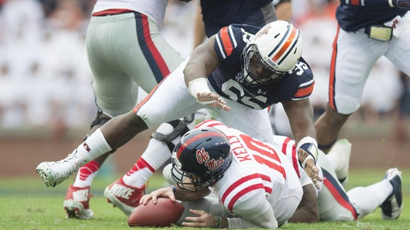Auburn Tigers defensive lineman Carl Lawson jumps on Ole Miss quarterback Chad Kelly as he recovers a fumble.