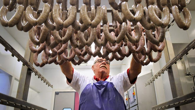 Steve Sellnow loads a rack with fresh sausages before they go into the smoker March 25 at St. Joseph Meat Market.