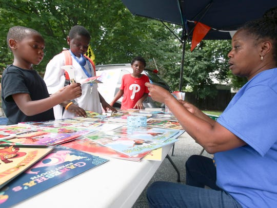 Tracye Burroughs helps neighborhood boys (from left) Nasir Harper, 8, Dre Hackett, 11, and Mike Money, 10, pick out books in a giveaway during a Southbridge Community event in July 2017.