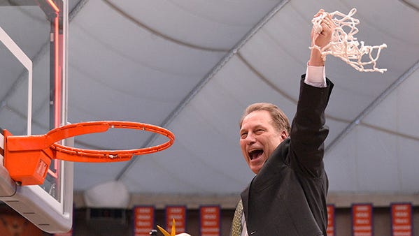 Tom Izzo waves the net to the Spartan crowd as MSU beats Louisville, 76-70, in the East Region final Sunday.