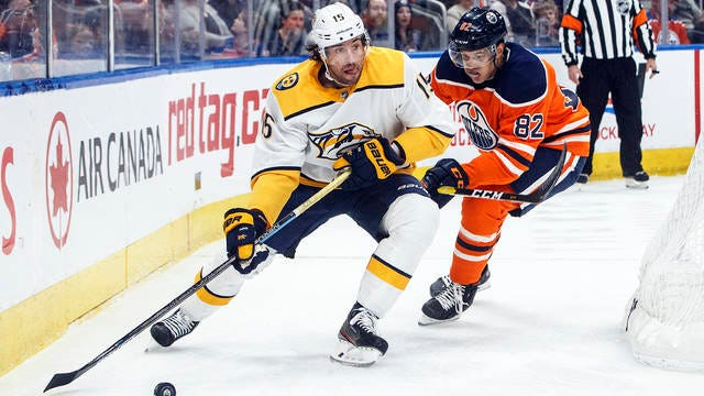 Nashville Predators' Craig Smith (15) is chased by Edmonton Oilers' Caleb Jones (82) during the first period of a NHL hockey game action in Edmonton, Alberta on Saturday.