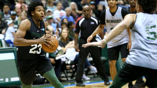 The Bucks' Sterling Brown (left) looks for an opening to shoot.