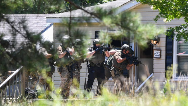 Members of the Anderson County SWAT team prepare to enter a home at 623 Campbell Rd. near Belton Sunday July 8, 2018. The officers were looking for the home's resident Austin Dalantinow, who was wanted on assault charges. Dalantinow was found hiding in the attic of a building beside the home.