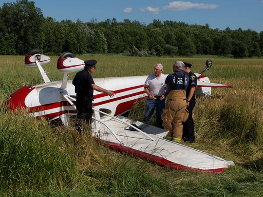 Monreo County Sheriff's Office and fire and rescue personnel look over the plane crash that occurred Saturday in Parma.