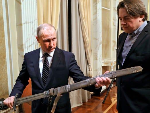 Russian President Vladimir Putin, left, holds a sword