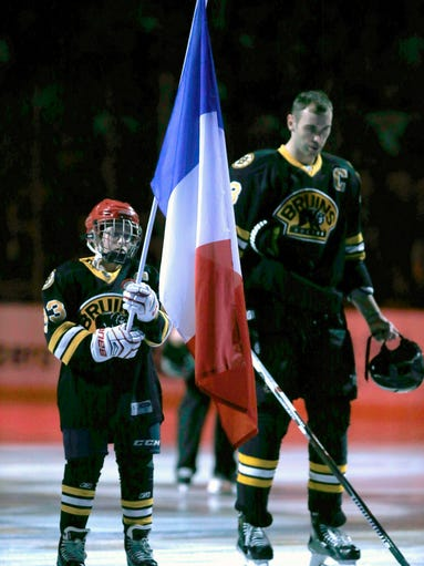 A young fan holds a French flag and stands on the ice