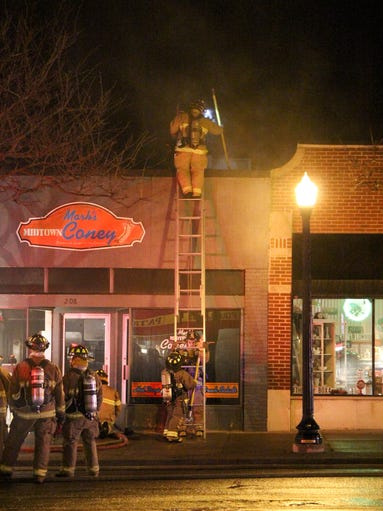 A Howell firefighter stands atop a ladder at the Mark's