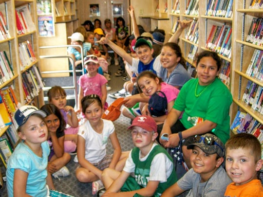 Children jump aboard the Rural Bookmobile East to read and browse through books. About 30 percent of the bookmobile's patrons are children.