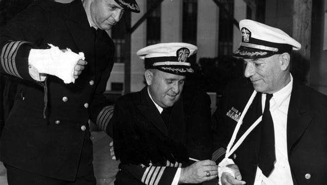Capt. Dixie Kiefer, center, signs one of the casts of Capt. George Mentz, right, at the Naval Medical Center in Bethesda, Md., on June 30, 1945. Looking on is Capt. Thomas Inglis. Kiefer was among six passengers of a Navy transport plane that crashed into Mount Beacon on Nov. 11, 1945.