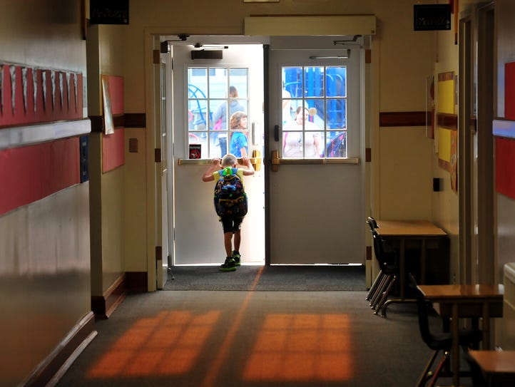 A student at Whittier Elementary School joins his classmates