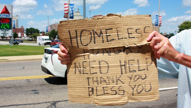 A panhandler stands on the corner of Capital Avenue Southwest and East Dickman Road Monday afternoon.