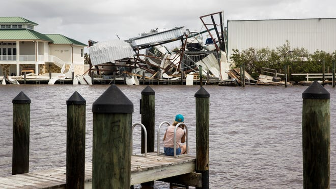 A woman looks across the channel to a demolished marina on Monday, Sept. 11, 2017, the morning after Hurricane Irma came through Goodland, Fla.