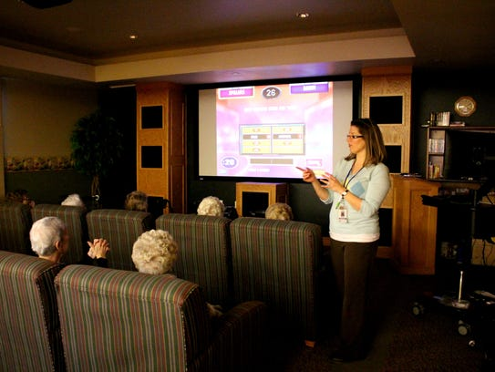 """Three Pillars' lifestyles manager Tina Rose projects iN2L technology in a group setting to lead a game of """"Family Feud."""""""