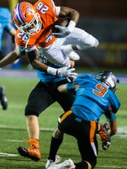Central's Otto Haynes jumps over Pebble Hills defenders during their Class 6A Division II bidistrict playoff game Friday, Nov. 17, 2017, at San Angelo Stadium.