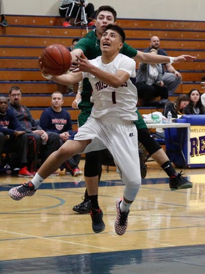 Tulare Western's Bryan Paredes lays the ball up against Dinuba during Tuesday's 66th annual Polly Wilhelmsen Invitational at Redwood High School in Visalia.