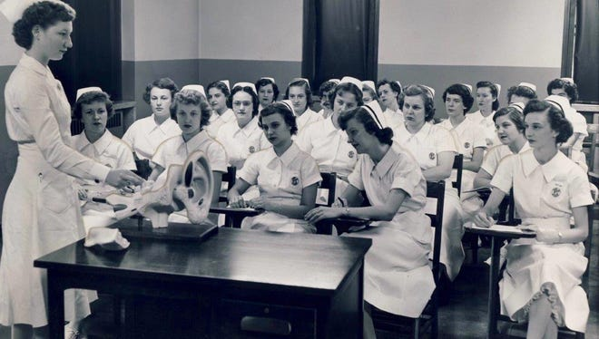 Clinical instructor Norma McCarroll, standing at left, teaches a class of student nurses in 1951 at Norton Memorial Infirmary, Third and Oak streets in Louisville.