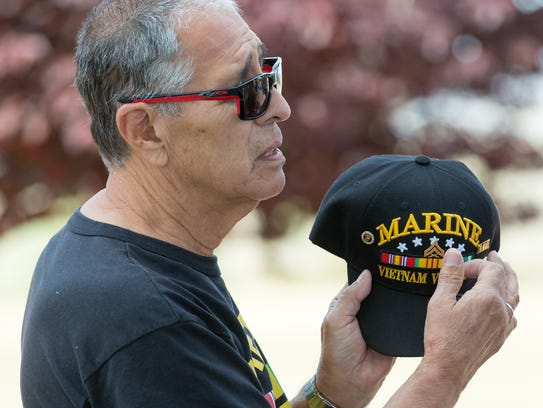 U.S. Marine Corp veteran Richard Sanchez takes his hat off and points to the insignia while talking with his twin brother U.S. Navy veteran William Sanchez, (not pictured) during the eighth annual Welcome Home Vietnam Veterans event at Veterans Memorial Park on Saturday, March 31, 2018. The twins served in Vietnam together.
