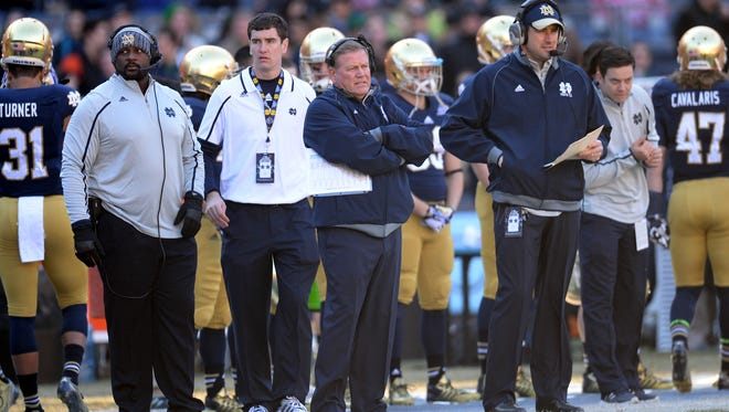 Notre Dame head coach Brian Kelly (center) looks on against Rutgers during the second half of the Pinstripe Bowl at Yankee Stadium in December.