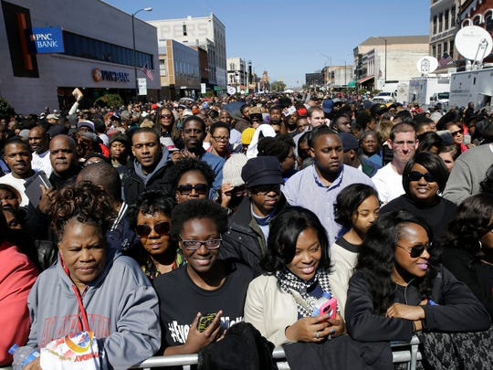 A large crowd forms near a stage where President Obama