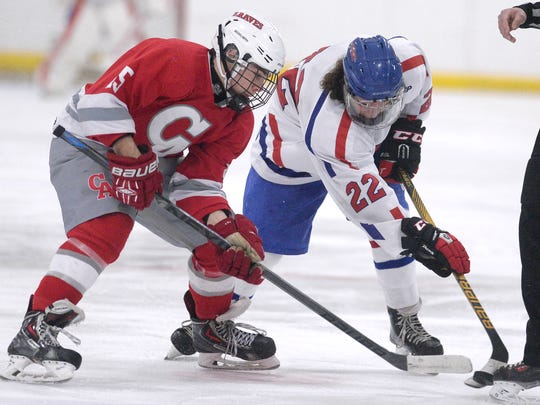 Fairport's Mason Eichmann, right, and Canandaigua's Alex Burley fight for the puck.