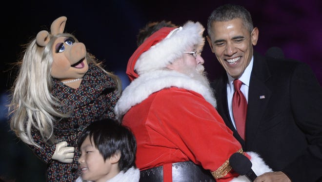 Miss Piggy, Santa Claus, and President Obama laugh on stage during the national Christmas tree lighting ceremony on the Ellipse south of the White House Dec. 3.