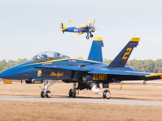 A Stearman airplane flies past the parked Blue Angels