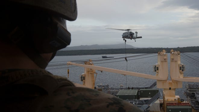 A Force Reconnaissance Marine with Maritime Raid Force, 31st Marine Expeditionary Unit, watches Marines fast rope out of an MH-60S Seahawk in Guam, January 31, 2018, during Visit Board Search and Seizure training. VBSS teaches Marines how to take over ships for searches and counter-piracy operations.  As the Marine Corps' only continuously forward-deployed MEU, the 31st MEU provides a flexible force ready to perform a wide range of military operations.