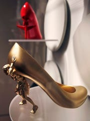 "In this Tuesday, Nov. 15, 2016 photo, a high heel shoe titled ""The Gold Digger"" by designer Sebastian Errazuriz, featuring a figure holding up the upper portion, is displayed at the Peabody Essex Museum in Salem, Mass., From flats to stilettos, what we put on our feet says something about who we are. That's the premise of new exhibition in Massachusetts. ""Shoes: Pleasure and Pain"" opens Saturday, Nov. 19, 2016, at the Peabody Essex Museum in Salem."