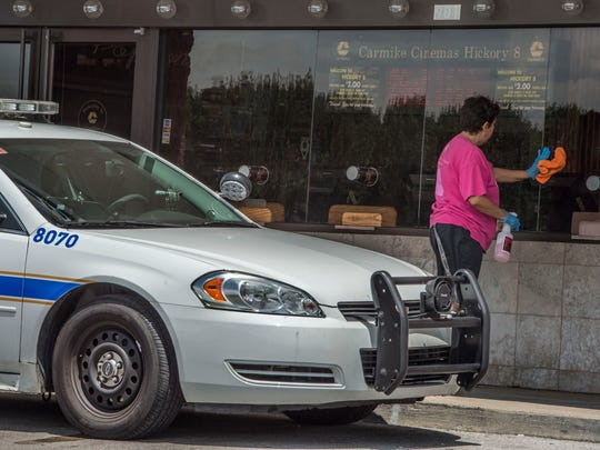 A Metro police car was outside the Carmike Hickory 8 theatre Monday, the day it was set to reopen to the public at 6:00 pm. a worker was seen cleaning up the box office window  on Monday Aug. 10, 2015, in Nashville in Tenn.