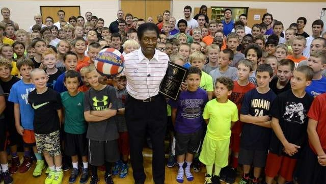 Ex-Globetrotter Hallie Bryant stands with campers Tuesday at Taylor basketball camp. Bryant was in his 58th year speaking at the camp.
