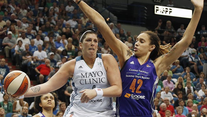 Minnesota Lynx's Janel McCarville (left) looks to pass the ball against Phoenix Mercury center Brittney Griner in the second half of a WNBA basketball game on July 31, 2014, in Minneapolis.