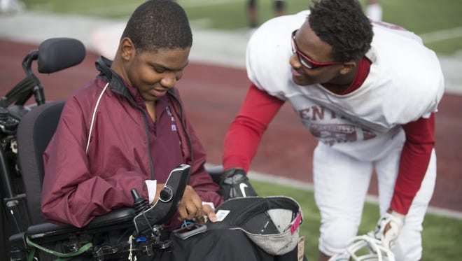 Emanuel Duncan, 18, who has Duchenne Muscular Dystrophy, confers with friend and player Bryan Rutland, 17, at a football practice for Lawrence Central High School.