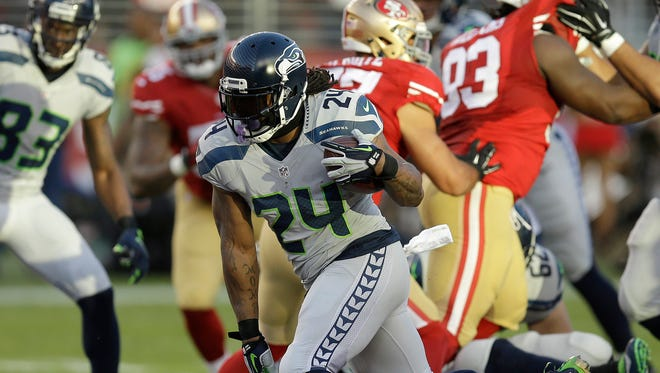 Seahawks running back Marshawn Lynch carries the ball in a 2015 game against San Francisco. Lynch is coming out of retirement to play for his hometown Oakland Raiders.