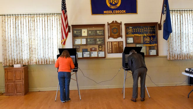 Mary Beth Barbagallo (left) of Middlebrook and James Champion of Staunton casts their ballots at the Middlebrook precinct during the primary elections on Tuesday, March 1, 2016.