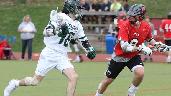 Rye's Seamus Carrol (8) guards Pleasantville's Jack Howe (18) during boys lacrosse game at Pleasantville High School on April 24, 2018.  Pleasantville defeats Rye 13-9.