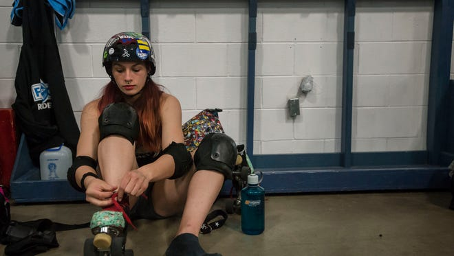 """Sydney """"Bruise Bury Ruffin"""" Edwards laces up her skates before a FoCo Roller Derby scrimmage on Thursday, March 22, 2018, at The Events Center in Fort Collins, Colo."""