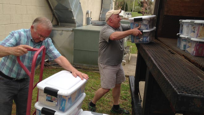Ron Allen, left, and Scott Witt, right, Gateway Christian Church members,  load up a box truck with 200 food boxes collected by Clarksville families.  These boxes are part of the Family to Family food program developed by World Compassion Network, Warsaw, Ind.