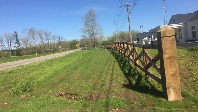 Agreements require for a path to be built in front of this fence running along the Weaver Road entrance way at Middleton. An agreement to delay construction until adjacent property development occurs has sparked controversy.